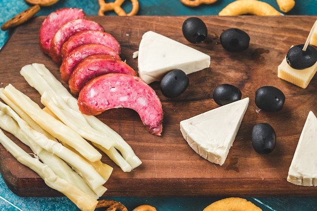 Snack board with sausage slices, cheese cubes and olives