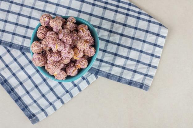 접힌 수건에 쉬고있는 스낵 그릇은 대리석에 캔디 코팅 된 팝콘으로 가득 차 있습니다.