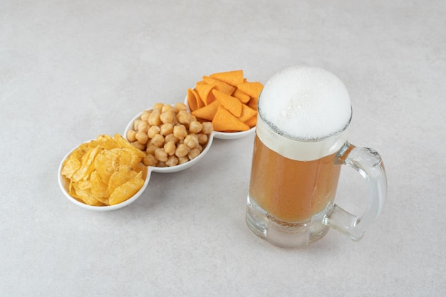 Snack bowls and glass of beer on stone surface