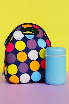 Snack on a break with a lunchbox. colorful handbag, blue thermos. lunch for a schoolboy or an office worker. place for text
