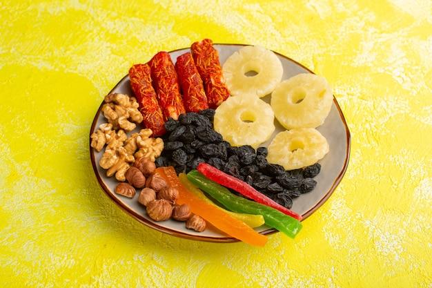 Закусочная композиция с сухофруктами, орехами, нугой и кольцами ананаса внутри тарелки на желтом