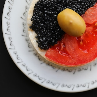 Snack cracker with tomato, black caviar and an olive.