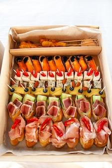 Закуска в картонной коробке с небольшими бутербродами, эклерами, брускеттой с мясным ассорти, сыром и морепродуктами для кейтеринга на шведском столе для вечеринки.