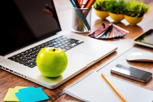 ビジネスの生産性のためのスナック。木製のテーブルとラップトップが置かれているオフィスの快適な職場のクローズアップ