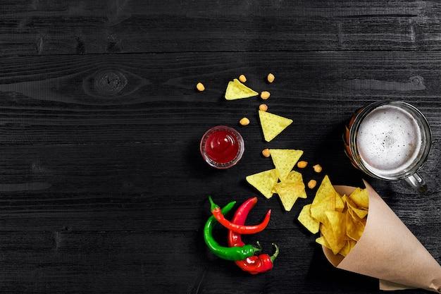 검정색 배경 상단 뷰 복사 공간에 소스와 맥주 한 잔을 곁들인 파티 칩 나초를 위한 스낵