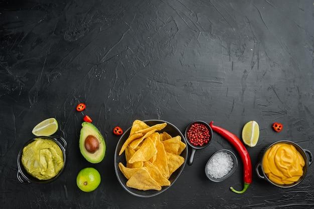Закуска для вечеринки, чипсы, начо с соусами, на черном столе, вид сверху или плоская планировка