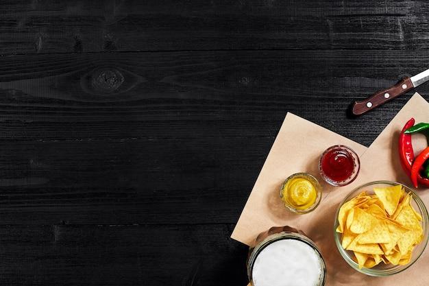 검은 배경에 소스 토마토 케첩 머스타드와 맥주 한 잔을 곁들인 파티 칩 나초를 위한 스낵...