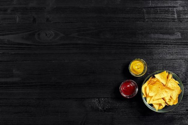검정색 배경 상단 뷰 카피에 소스 토마토 케첩 머스타드를 곁들인 파티 칩 나초를 위한 스낵...