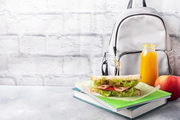 サンドイッチ、新鮮なリンゴ、オレンジジュースを使った学校のおやつ。カラフルな学用品、コピースペース、