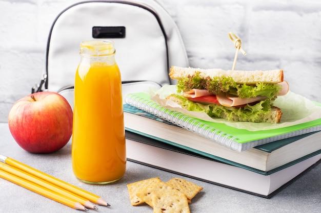 サンドイッチ、新鮮なリンゴ、オレンジジュースを使った学校のおやつ。カラフルな学用品、