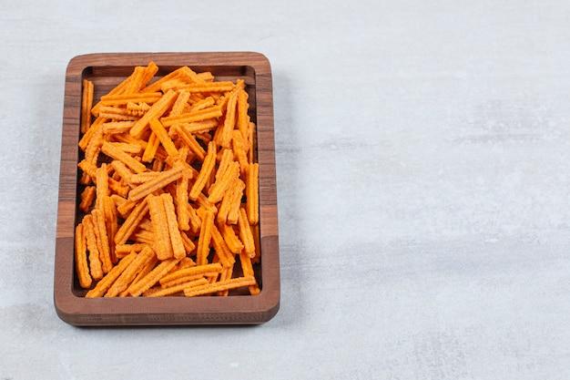 Merenda. chip freschi sul piatto di legno.