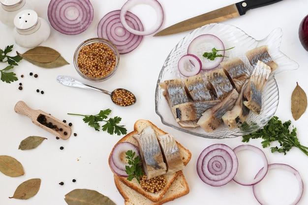 흰색 배경에 붉은 양파와 겨자를 곁들인 빵에 소금에 절인 청어의 간식, 상위 뷰