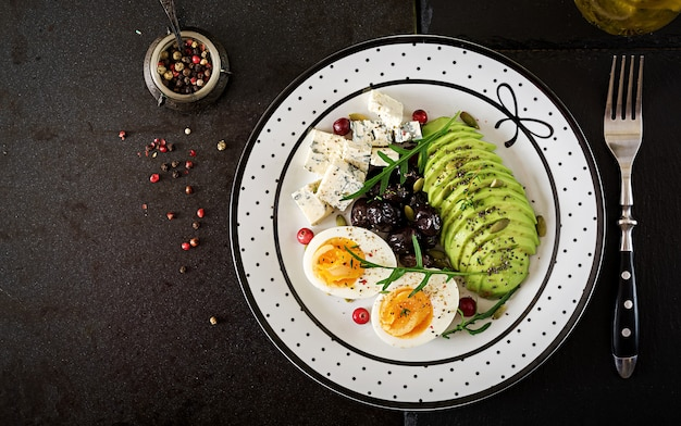 Snack or healthy breakfast  - plate of blue cheese, avocado, boiled egg, olives on a black table.