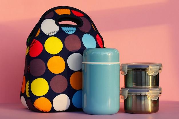 お弁当箱のカラフルなハンドバッグの青い魔法瓶と食べ物の入った2つの金属製の容器で休憩をとってください...