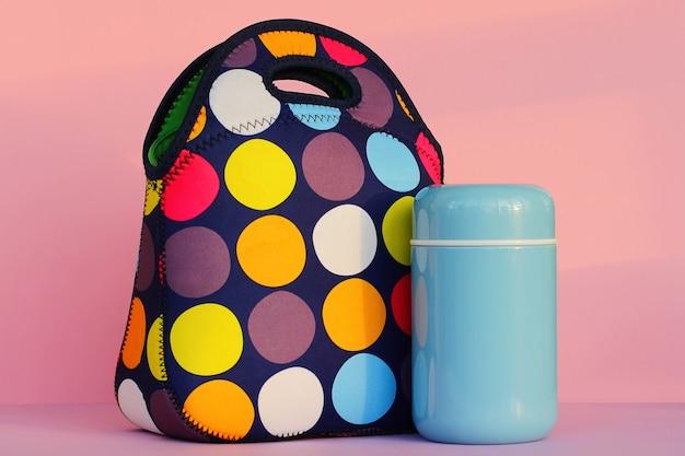 男子生徒やオフィスでお弁当箱のカラフルなハンドバッグの青い魔法瓶ランチで休憩をとる...