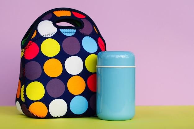 お弁当を持って休憩を取りましょう。カラフルなハンドバッグ、青い魔法瓶。男子生徒やサラリーマンのための昼食。テキストの場所