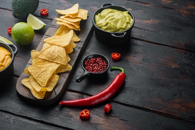 Snack for party, chips, nachos with sauces, on old wooden table