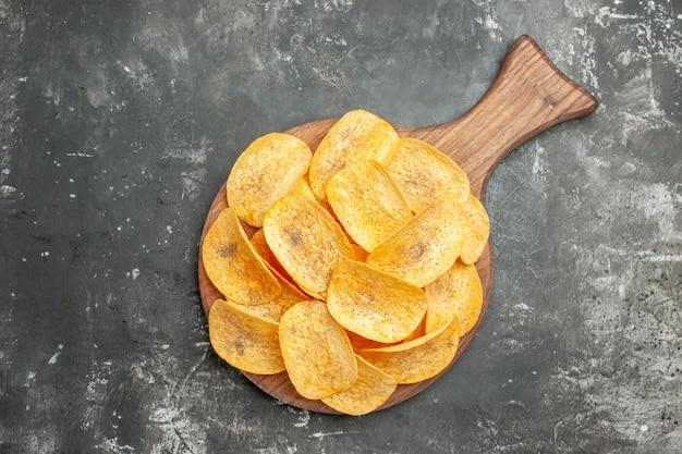 회색 테이블에 맛있는 수제 칩과 감자와 함께 친구를위한 스낵 파티