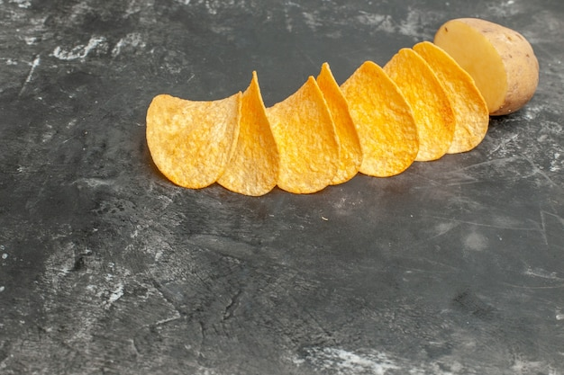 Snack party for friends with delicious homemade chips and potato on gray background