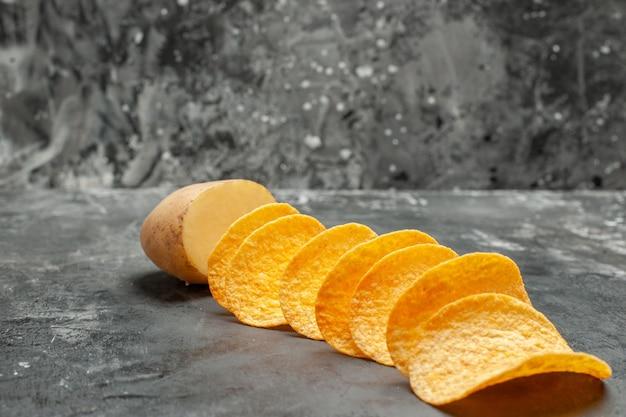 Snack party per gli amici con deliziose patatine fatte in casa e patate su sfondo grigio