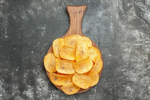 Snack party per gli amici con deliziose patatine fatte in casa sul tagliere di legno sul tavolo grigio