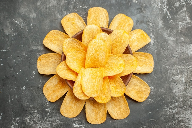 Snack party for friends with delicious potato chips on gray background