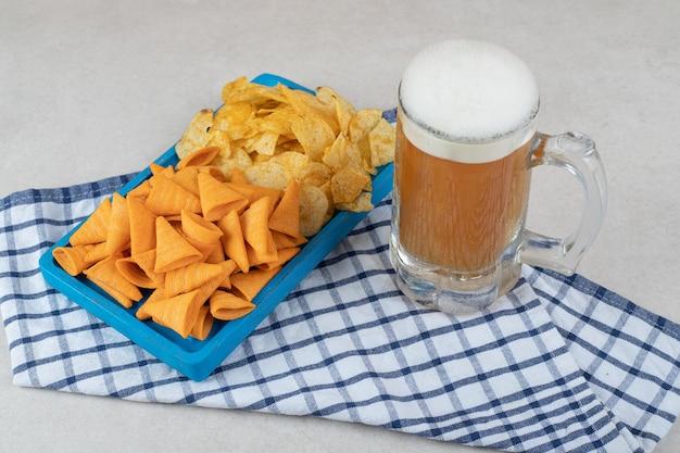 Piatto di snack e bicchiere di birra sulla tovaglia