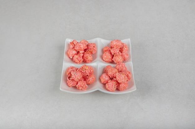 大理石のテーブルにポップコーンの砂糖漬けの4つの部分とスナックの盛り合わせ。