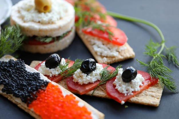Snack sandwiches caviar and vegetable.