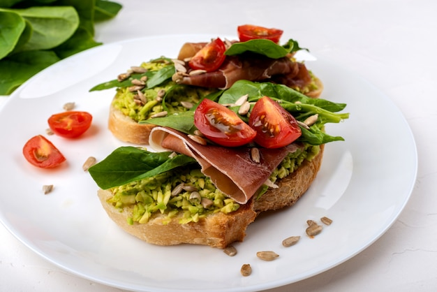 Snack sandwiches with jamon, avocado, tomatoes and leaf salad.