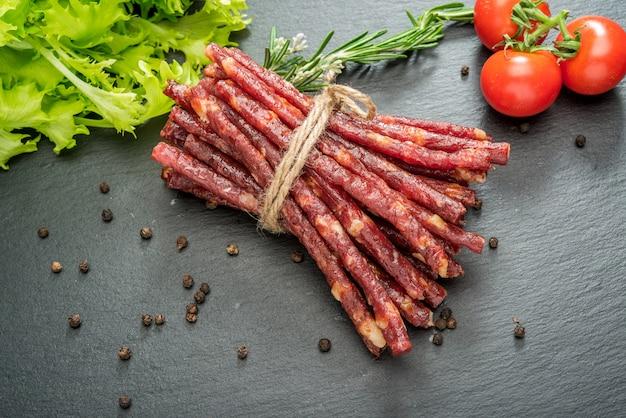 Закусочные колбасные палочки на деревянном столе