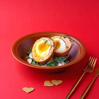 스낵-스코틀랜드 계란. 접시에 연어, 무, 시금치와 스코틀랜드 계란