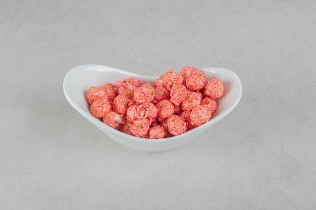 Snack che serve popcorn rosso caramelle in una ciotola ovale sul tavolo di marmo.