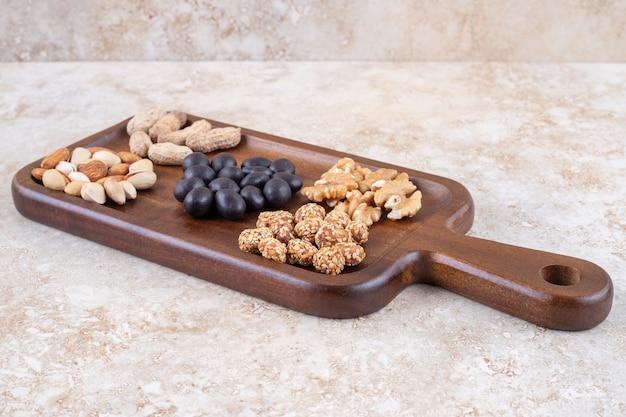 Подача закуски с небольшими стопками орехов и конфет на доске