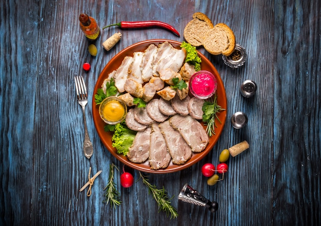 Snack set. assorted sliced meat with spices on rustic wooden background