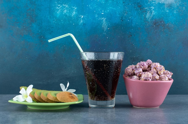 Snack set of sliced kiwis, glass of cola and a bowl of popcorn candy on blue