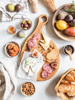 スナックセットテーブル。さまざまなチーズ、オリーブ、ソーセージ、バゲットスライス、イチジク、木の板のナッツ、フラットレイ。上面図。