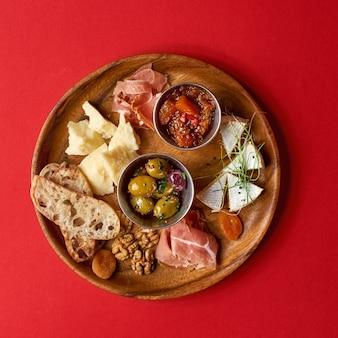 Закусочная. разнообразие сыра, оливки, прошутто, жареные ломтики багета, выборочный фокус, квадратный урожай.