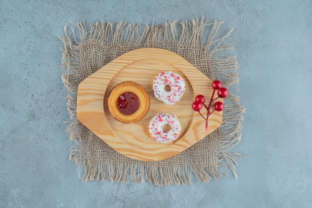 Ciambelle a grandezza naturale e una torta di gelatina su un vassoio di legno su fondo di marmo. foto di alta qualità