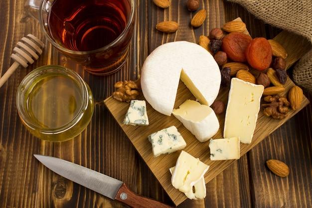 木製のまな板の上にチーズ、お茶、蜂蜜とスナック。上からの眺め。