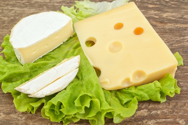 Snack on a wooden table from two types of cheese on a piece of lettuce.