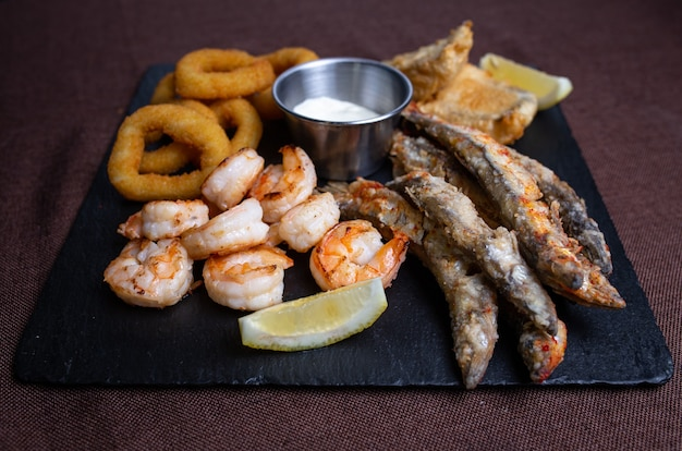 Snacks to beer on a black plate of fish and onion rings.