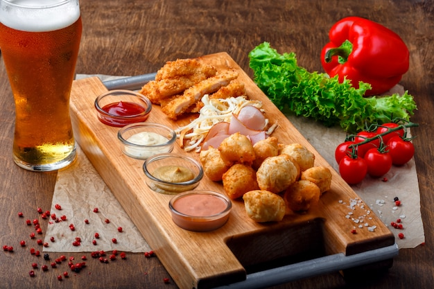 Snacks for beer it includes fried cheese balls, pigtail cheese, ham and crab sticks on a wooden board