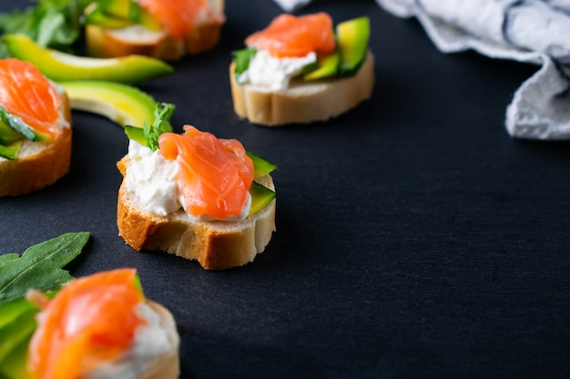 Snacks, bruschetta with cream cheese, avocado and salmon