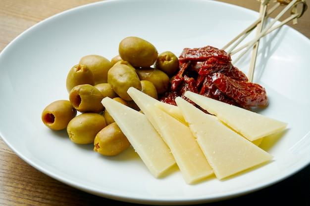夕食のおつまみ。オリーブ、ハードチーズ、天日干しトマトの前菜プレート。見る