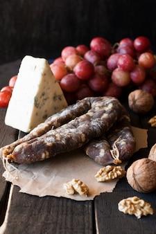 Закуски к вину, сыр с плесенью, розовый виноград, грецкие орехи и сыровяленая колбаса
