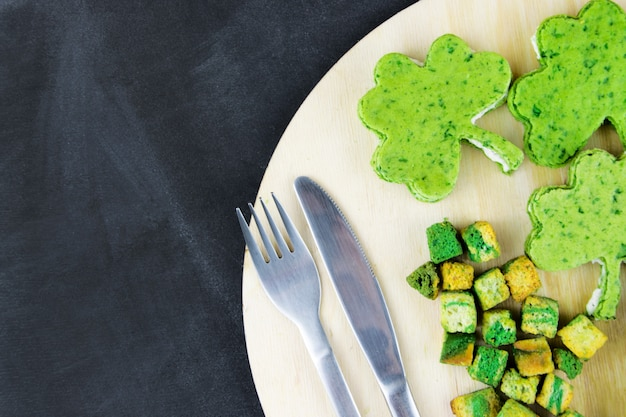 Snacks of green color with a fork and knife. working space, the concept of st. patrick