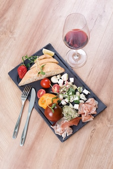 Snacks with red wine on black slate board over wooden background