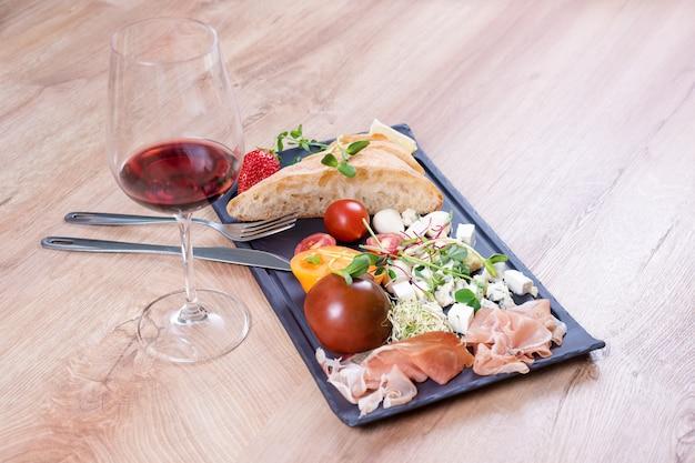 Закуски с красным вином на черной грифельной доске над деревянными
