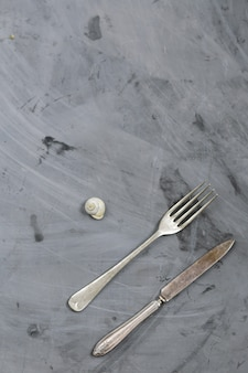 Snail, fork and knife on grey concrete background. copy space.